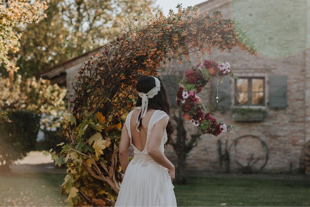 Un arco floreale a forma di mezzaluna per un matrimonio autunnale e bohémien