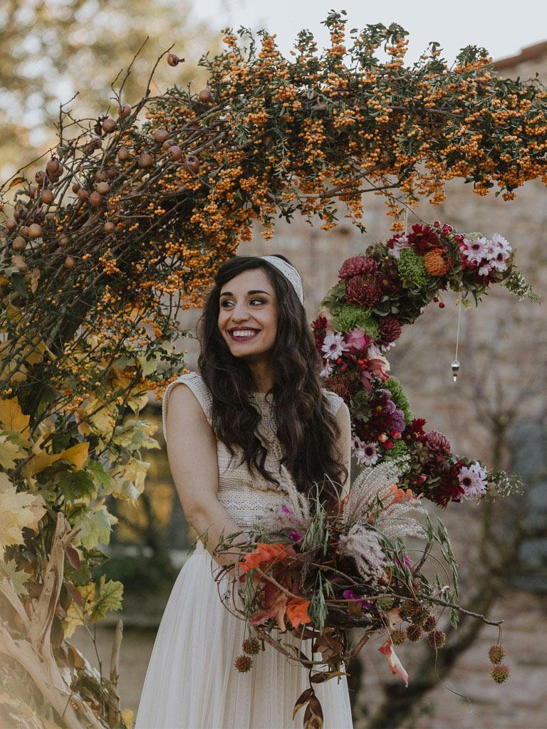 Una sposa davanti a un arco floreale a forma di mezzaluna