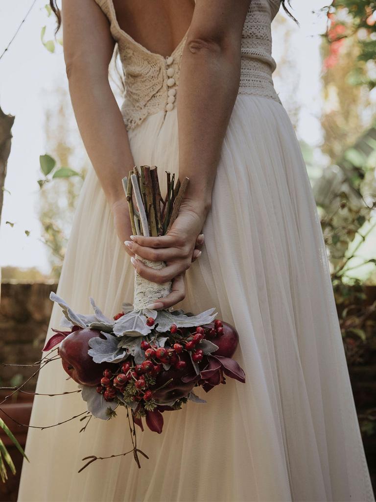 Una sposa di schiena che tiene in mano un bouquet di mele durante un matrimonio autunnale