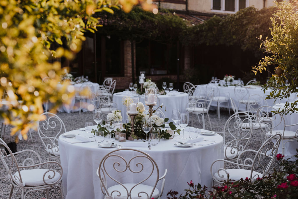 La mise en place e le decorazioni floreali di un tavolo per un matrimonio in un giardino a Venezia