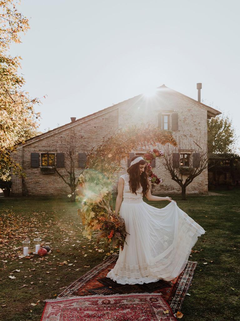 Una sposa davanti a un arco floreale a mezzaluna durante un matrimonio autunnale e bohémien