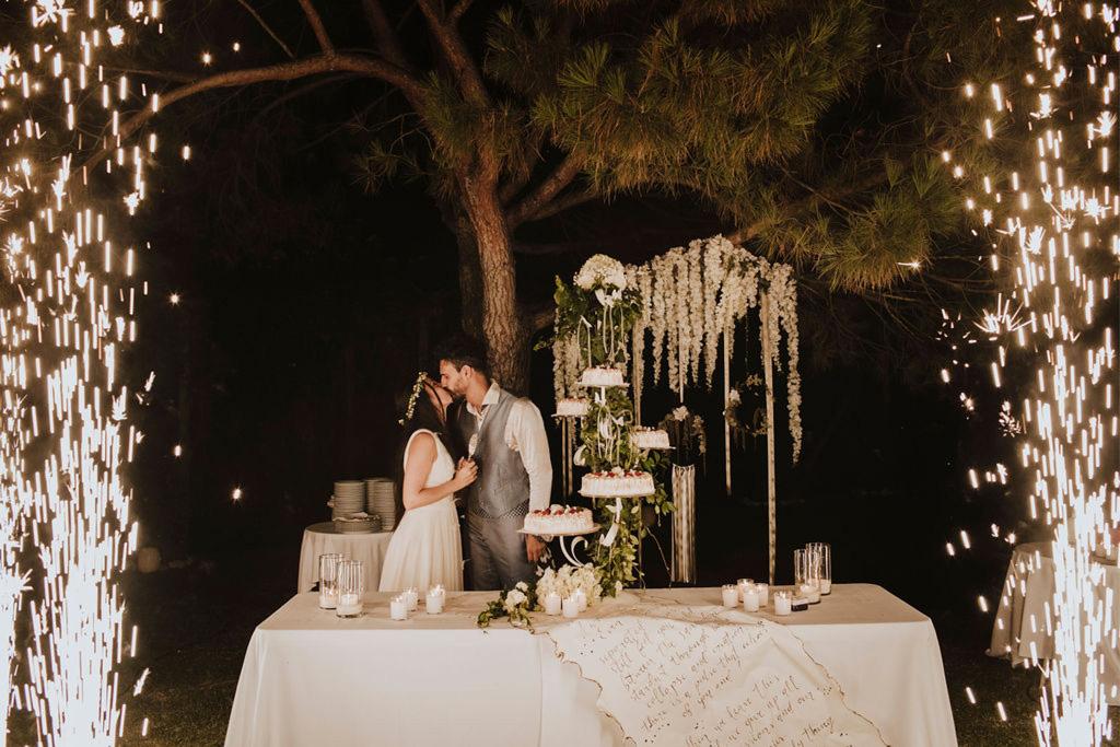 Il momento del taglio torta durante un matrimonio in un giardino di Venezia